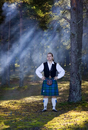 Handsome man in scottish costume in the forest photo