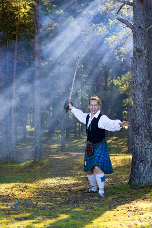scot: Screaming man in scottish costume with sword in the forest