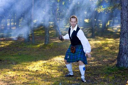 highlander: Valiente en el traje escocés con la espada en el bosque Foto de archivo