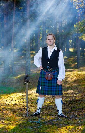 highlander: Hombre valiente en traje escocés con la espada en el bosque