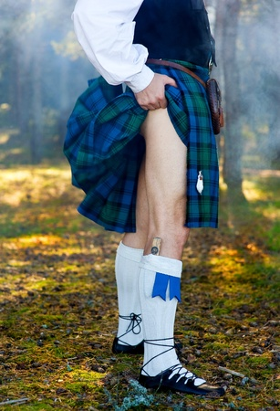Legs of the man in kilt outdoor Stock Photo