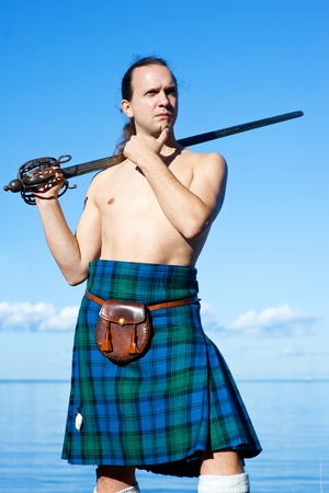 Man with naked torso in kilt on the sky background
