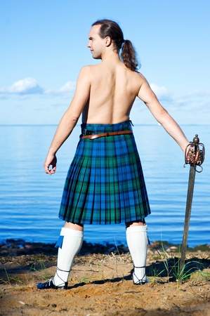 Man with naked torso in kilt on the sea background