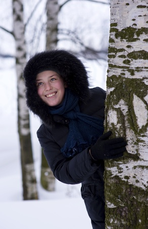 lean out: Young girl looks out from the tree