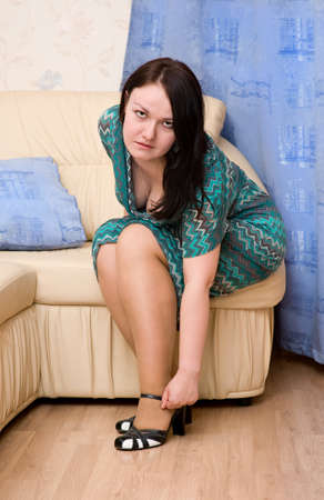 Woman putting on her shoes at home photo