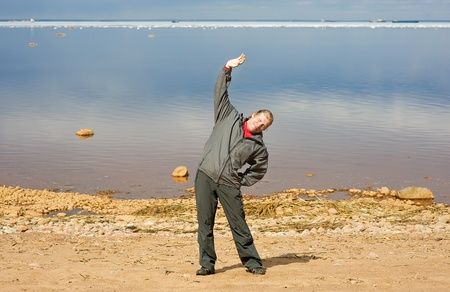 Man doing exercises on the sand photo