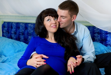 Pregnant couple in the blue bed Stock Photo - 11874445