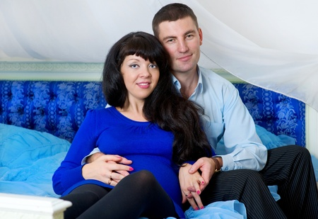 Pregnant couple in the blue bed photo