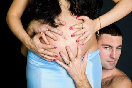 Pregnant couple holding belly by hands on the black background Stock Photo - 11874447
