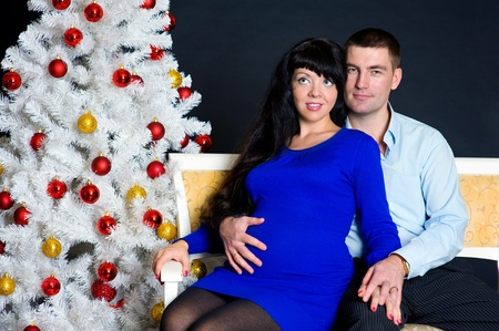 Beautiful pregnant couple with christmas tree photo