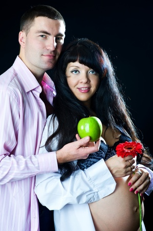 Pregnant couple with apple and flower on the black background photo