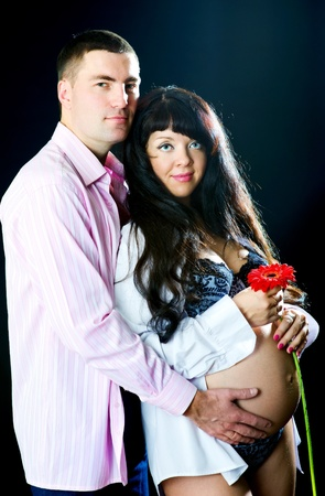 Pregnant couple with red flower on the black background photo