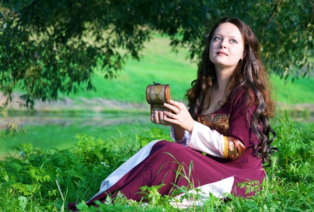 middeleeuwse jurk: Vrouw in middeleeuwse kleding met oude kist