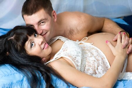 Pregnant couple smiling and hugging in the bed photo