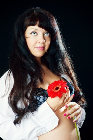 Pregnant woman with red flower photo