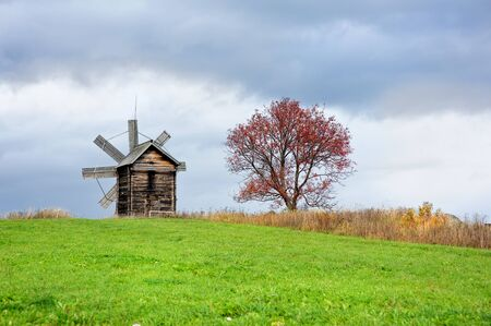 hillock: Old wind mill and the tree on the hillock Stock Photo