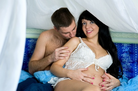 Pregnant smiling woman with her husband in the bed photo