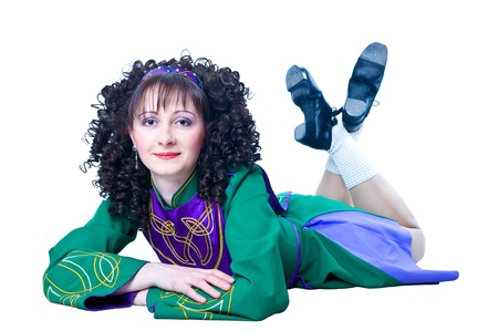 Woman irish dancer lying on the white background photo