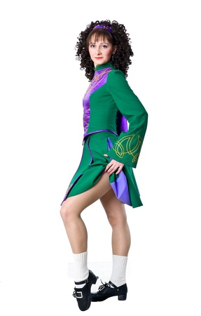 Beautiful woman Irish dancer posing in the green dress photo