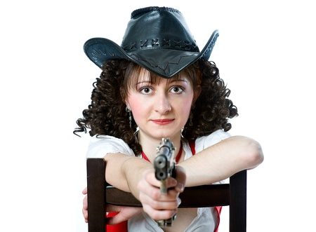 Beautiful woman in cowboy hat with gun sitting on the chair photo