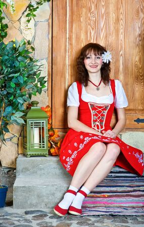 doorstep: Beautiful woman in the red dress sitting on the doorstep Stock Photo