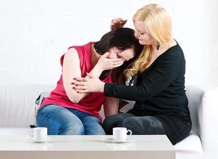 personas abrazadas: La mujer consuela a su amiga sentada en el sof� Foto de archivo