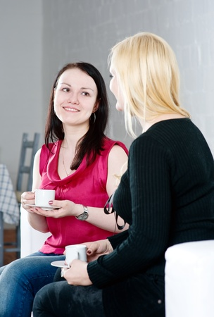 Two beautiful women drinking coffee and talking photo