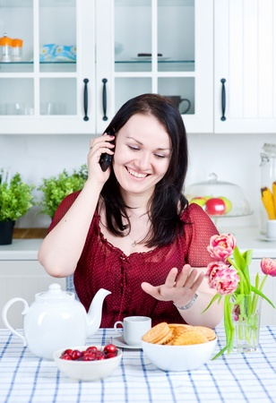 Beautiful happy woman talking on phone at home photo