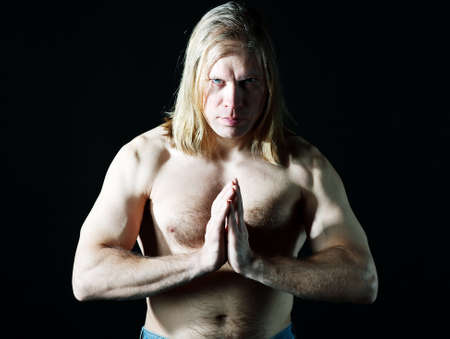 Man with naked torso doing yoga  photo