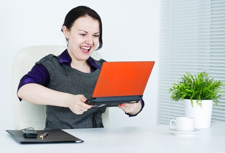 annoyance: Angry business woman throwing laptop
