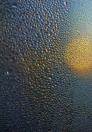 Waterdrops and sun on the window surface photo