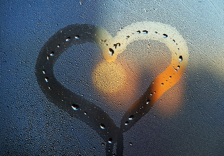 Heart from dew drops and sun on the window