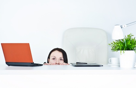 Business woman hiding behind table and afraid photo