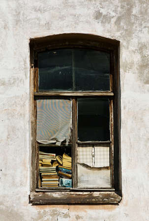 Old window with books and old wall photo