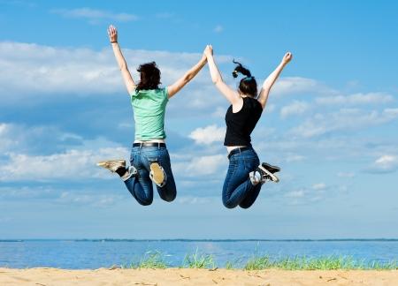 Twee jonge gelukkige vrouwen springen op het strand Stockfoto