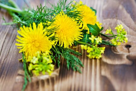 Yellow flowers and grass on the wood background Stock Photo - 13860092