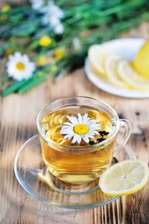 Tea with chamomile, lemons and herbs on the wood background photo