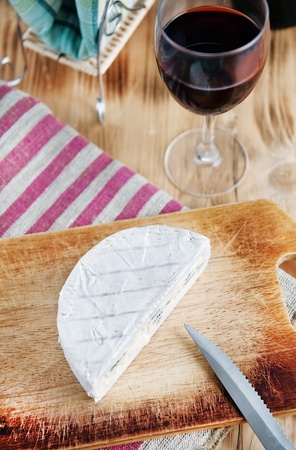 Blue cheese on the wooden board, knife and wine  photo