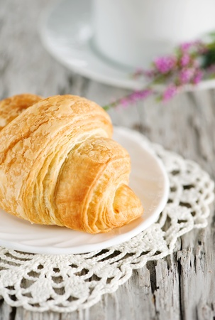 Croissants with cup of coffee on the old wooden background photo