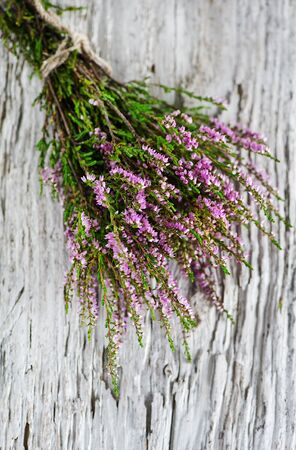 Bouquet of heather on the old wood background photo