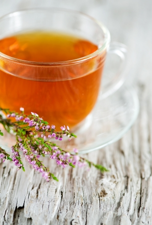 Cup of tea and heather on the wooden background photo