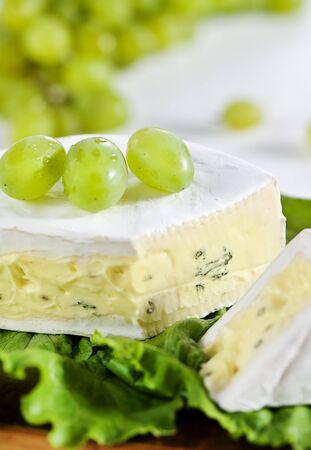 Cheese with blue mould and grape photo