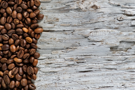 Coffee beans on the old grunge wood background photo