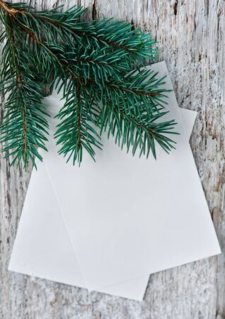 Christmas cards with fir branch on the old wood background photo
