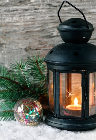 Burning lantern with fir branch on the old wood background photo