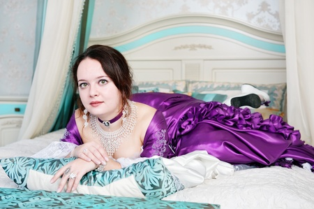 Beautiful young woman in medieval dress lie on the bed photo
