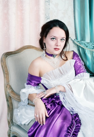 Beautiful young woman in medieval dress sitting on the chair photo