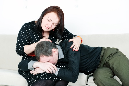 Woman comforting her crying man on the sofa photo