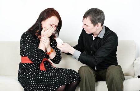 Man comforting his crying man on the sofa photo
