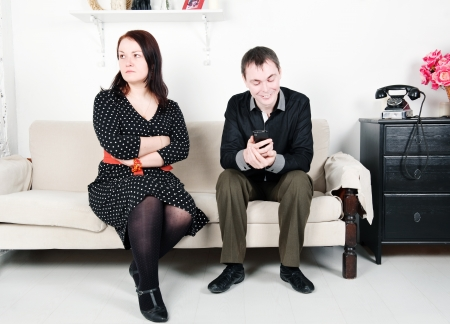 Jealous woman looking at her man chatting on telephone photo